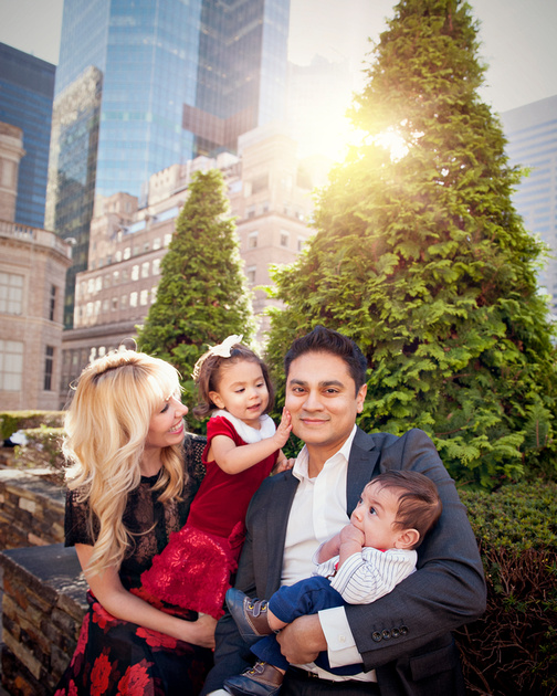 a gorgeous family on top of rockefeller center poses for a portrait session of a lifetime.